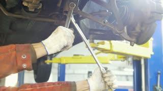 Automobile diagnostic - mechanic working under a lifted car, de-focused background