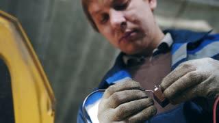 Automotive electrician checks electro relay in car, small business - auto garage service, bottom view