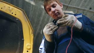 Automotive electrician checks electro relay in car, small business - auto garage service