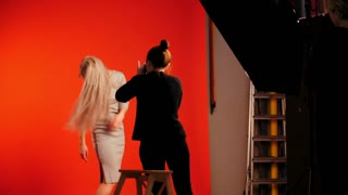 Backstage: photo session in studio with girl model - plays long blonde hair