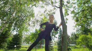 Beautiful little girl doing gymnastics exercises on the grass at summer