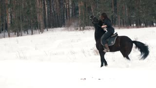 Beautiful longhaired woman riding a black horse through the snow in the forest