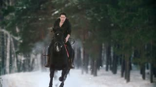 Beautiful longhaired woman riding a brown horse through the deep snowbank in the forst, slow-motion