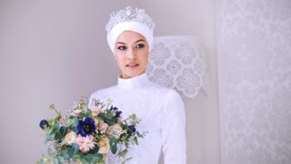 Beautiful model in white muslim wedding dress and bridal headdress with flowers