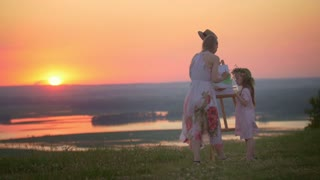 Beautiful mother and daughter drawing in nature on the hill at sunset
