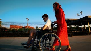 Beautiful Red-Haired Girl Rolls Guy In A Wheelchair On The Promenade In The Evening