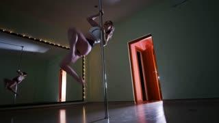 Beautiful slim girl exercising pole dance in a studio