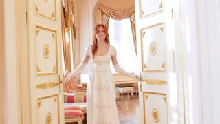 Beautiful woman in a ball gown opens the door