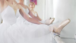 Beautiful young ballerinas on pointe exercises at ballet bar in a studio