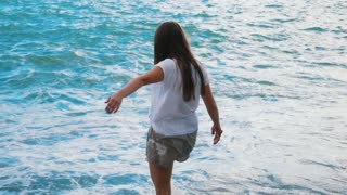 Beautiful young girl having fun playing with the waves of the amazing sea