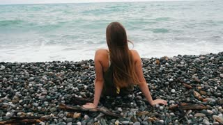 Beautiful young girl sits on the rocks, straightens her hair and enjoys a refreshing breeze and a beautiful view of the sea