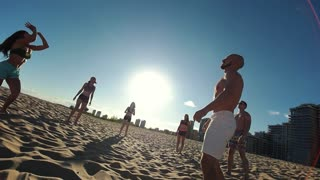 Beautiful young sports people play beach volleyball in the summer evening in the sun