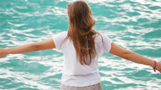 Beautiful young woman having fun playing with the waves of the amazing sea