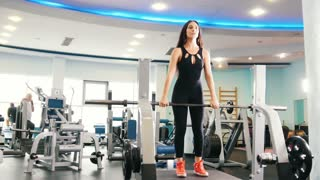 Black hair woman exercising in gym - lifts up the weight