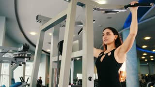 Black hair woman exercising in gym - training for shoulders