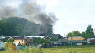 Black smoke poured behind houses in the village