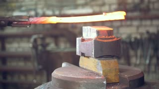 Blacksmithing forging on an anvil in the forge