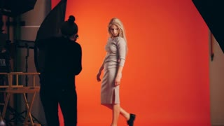 Blonde girl posing for photographer - model stands near red background