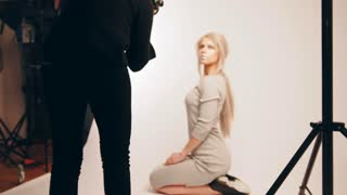 Blonde handsome girl posing for photographer - fashion backstage, model sits at knees