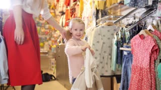 Blonde little girl with mother buying dresses - kids clothes in store
