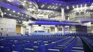 Blue chairs in a concert hall, blurred