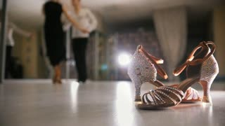 Blurred man and woman dancing Latin dance in costumes in the Studio, ballroom shoes in the foreground, slow motion