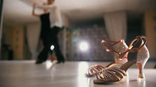 Blurred professional man and woman dancing Latin dance in costumes in the Studio, ballroom shoes in the foreground, slow motion