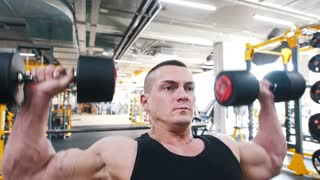 Bodybuilder in a black tank top performs a dumbbell shoulder press exercise sitting in a chair