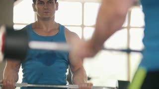 Bodybuilding in the gym - muscular man training his biceps near mirror