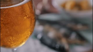 Boubles in glass of beer in front of dried fish