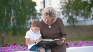 Boy and grandmother read fairy tales in the park