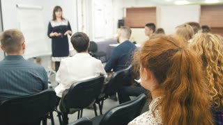Business woman at seminar - speaker female teaching at international conference, de-focused shot