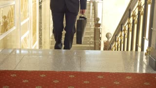 Businessman in suit climbing up the stairs in the office building