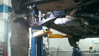 Car auto service - mechanic checks details of car under bottom of vehicle