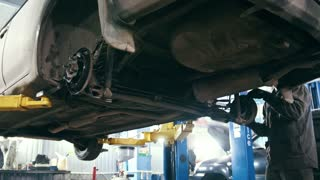 Car auto service - mechanic repairs of the car - works under bottom of vehicle