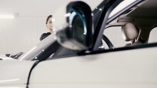 Car detailing - attractive young woman is cleaning windshield of a luxury vehicle