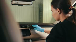Car detailing - woman in blue gloves cleans vekicle head panel - dashboard