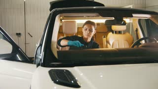 Car detailing - woman is cleaning dashboard in luxury vehicle