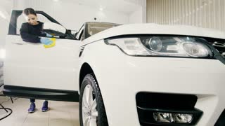 Car detailing - woman is cleaning luxury vehicle