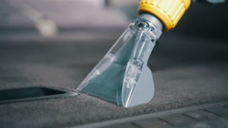 Car interior cleaning with vacuum cleaner, carpeted in the trunk
