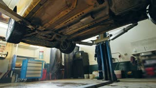 Car lifted in automobile service for checking, worker repairs detail