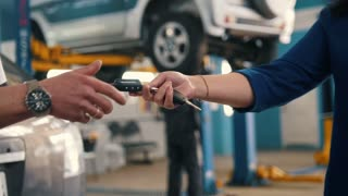 Car workshop - woman gives the keys of car for mechanic