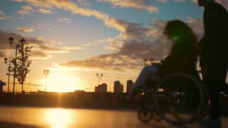 Caring man with a disabled woman in wheelchair walking through the quay at sunset