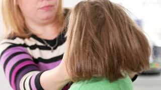 Caring mom is combing hair her little daughter