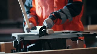 Carpenter cutting wooden plank with dangerous circular electric saw