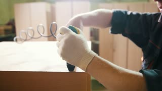 Carpenter working with an electric industrial stapler on the factory, fixing furniture details, close-up