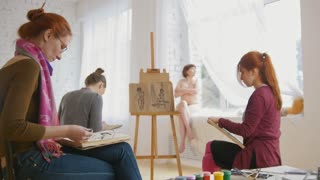 Caucasian female artists performing artistic etude witn naked model in drawing studio