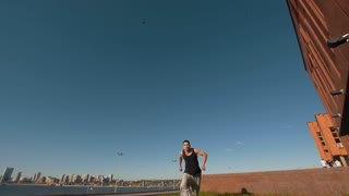 Caucasian young man performs acrobatic flips on the background cityscape at sunny day