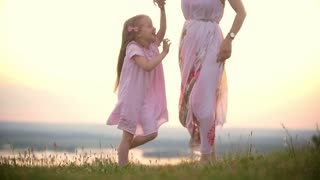 Cheerful little girl holding hands her mom dancing on the grass hill at summer sunset