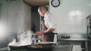 Chef cooking spaghetti in restaurant